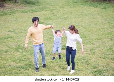Parenting young Japanese family playing in the park,