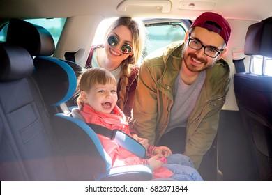 Parents adjusting baby seat