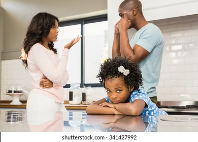 Parents arguing in front of daughter in the kitchen
