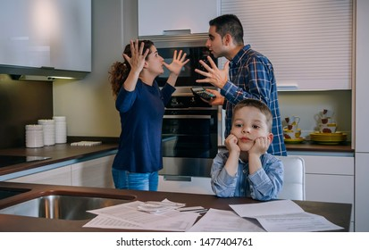 Parents arguing heatedly in the kitchen with their little son in front