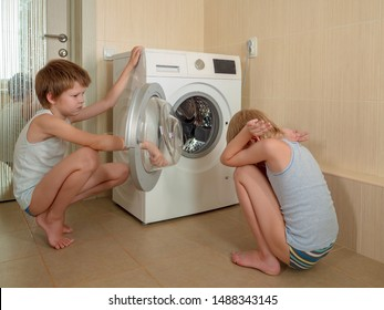 Parents bought new washing machine of latest modification. Children try to turn it on and wash soft toys. Happy boys play at home.
