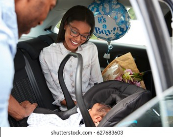 Parents Bringing Newborn Baby Home In Car