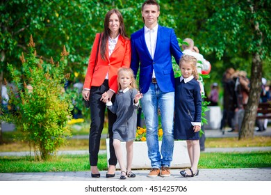 Parents brings theiir little cute daughters to school. Adorable little girls feeling very excited about going back to school