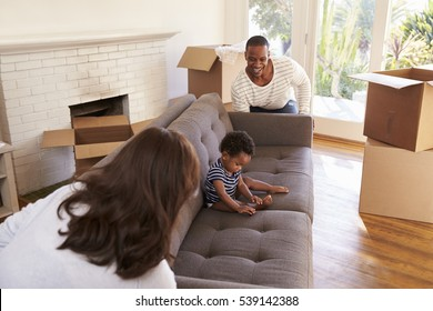 Parents Carry Son On Sofa Into New Home On Moving Day