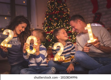 Parents celebrating New Years Eve at home with kids, sitting by the Christmas tree, holding illuminative numbers 2021 representing the upcoming New Year