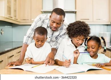 Parents checking children homework in the kitchen
