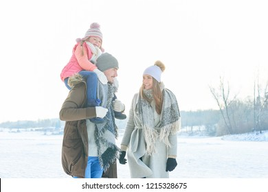Parents with child as family in winter taking a walk with a piggyback ride