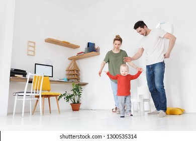 Parents and child at home. Mom and daddy playing with their little son in white domestic interior. Parent and little kid relaxing at cozy house. Family having fun together at the weekend