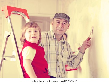 Parents with child  paints wall at home