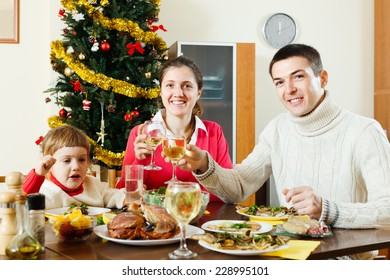 parents and child posing for  Christmas portrait around festive table at home