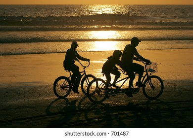 Parents and a child riding bikes along the beach at sunset