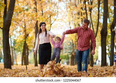 Parents and child are walking in autumn city park. Bright yellow trees.