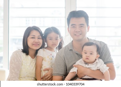 Parents and children. Asian family spending quality time at home, natural living lifestyle indoors.