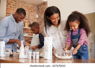 Parents And Children Baking Cakes In Kitchen Together