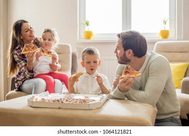 Parents with children eating pizza together and having fun in living room