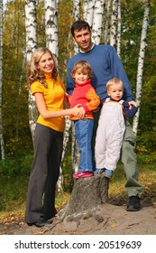 Parents with children in forest in autumn