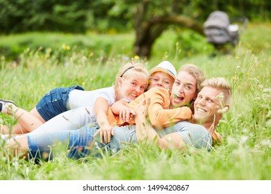 Parents and children have fun and laugh together in the grass in the garden
