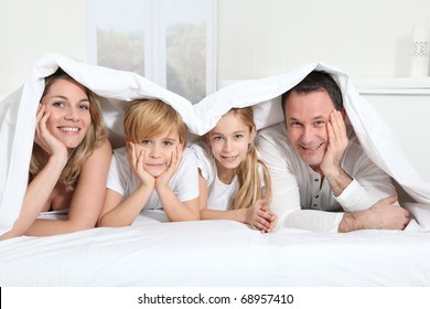 Parents and children laying in bed in the morning