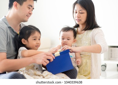 Parents and children open gift box together. Asian family spending quality time at home, natural living lifestyle indoors.