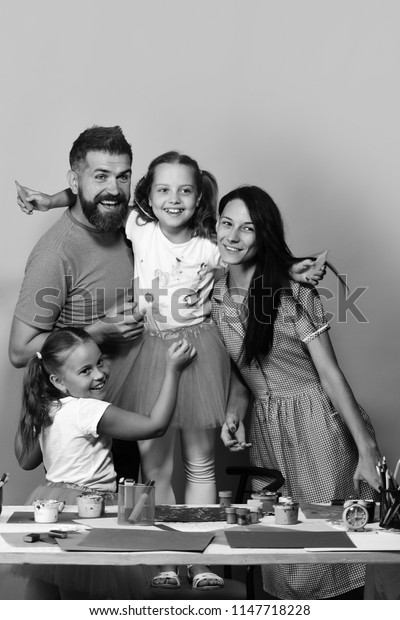 Parents and children paint with markers and smile. Artists family hugs on pink background. Creativity and family concept. Girls, man and woman with happy smiling faces by their art desk.