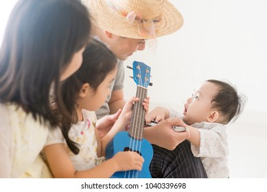 Parents and children playing music instruments together. Asian family spending quality time at home, natural living lifestyle indoors.
