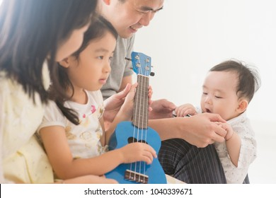 Parents and children playing ukulele together. Asian family spending quality time at home, natural living lifestyle indoors.