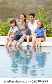 Parents with children relaxing by the pool