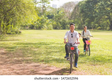 Parents and children are riding a bicycle in the park in the morning with a smiling and happy face with a tree background. with copy space