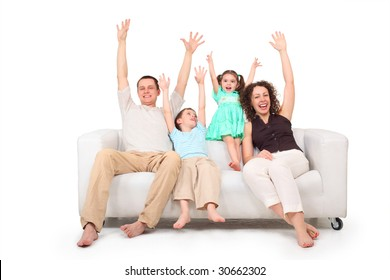 Parents and children with rised hands  on white leather sofa
