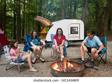 Parents with children roasting marshmallows on campfire with teardrop camper in background.