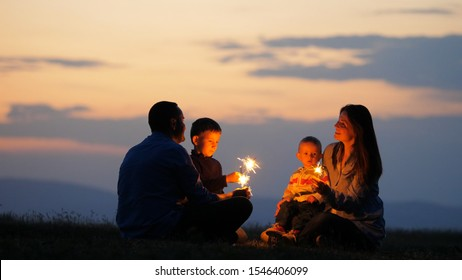 Parents and children silhouettes holding fireworks sparklers, sunset sky, celebration in nature