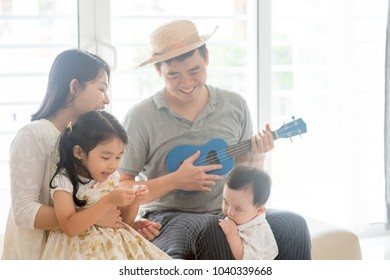 Parents and children singing and playing music instruments together. Asian family spending quality time at home, natural living lifestyle indoors.