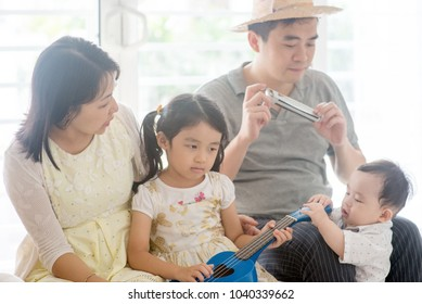 Parents and children singing and playing ukulele and harmonica together. Asian family spending quality time at home, living lifestyle indoors.