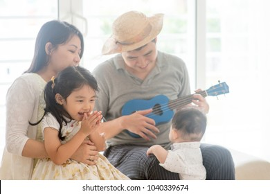 Parents and children singing and playing ukulele together. Asian family spending quality time at home, natural living lifestyle indoors.