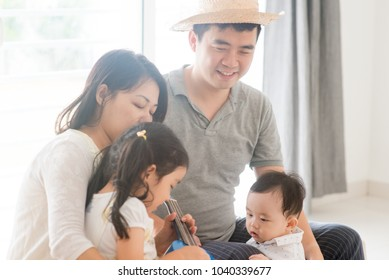 Parents and children singing and playing ukulele together. Asian family spending quality time at home, living lifestyle indoors.