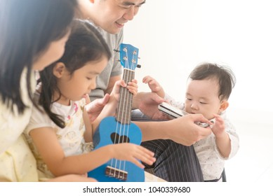 Parents and children singing and playing ukulele and harmonica together. Asian family spending quality time at home, natural living lifestyle indoors.