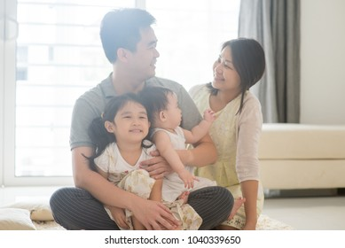 Parents and children sitting on floor together. Happy Asian family spending quality time at home, candid living lifestyle indoors.