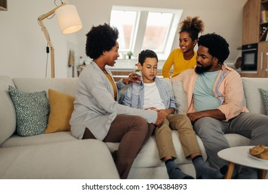 Parents and children sitting on sofa in the living room and socializing