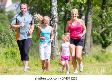 Parents with children sport running together through forest