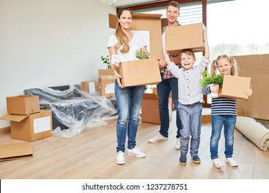 Parents and children together carry moving boxes to the new home