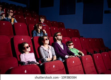 Parents with children watching a comedy in 3D movie