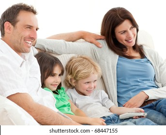 Parents and children watching television together on the sofa