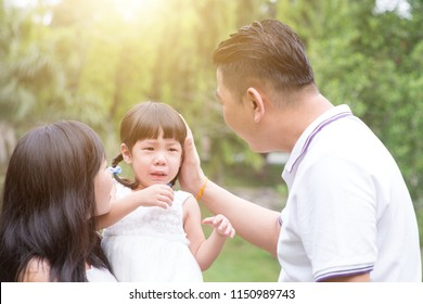 Parents comfort crying daughter at outdoor garden park. Asian family outdoors portrait.