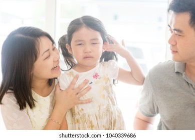 Parents comforting crying child. Asian family at home, natural living lifestyle indoors.