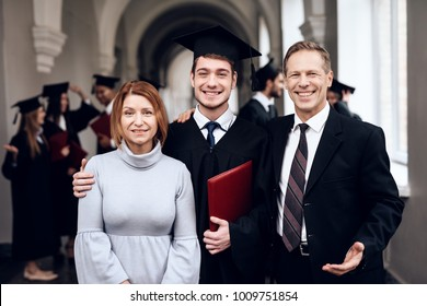 Parents congratulate the student, who finish their studies at the university. He graduates. They are very happy about this.