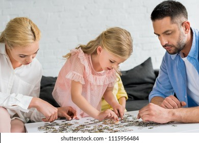 parents with cute little daughter playing with puzzle pieces at home