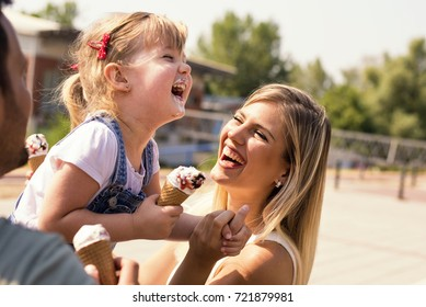 Parents and daughter eating ice cream and having fun outside