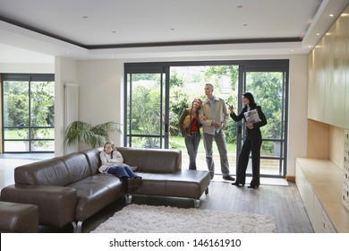 Parents with daughter and female estate agent observing new property