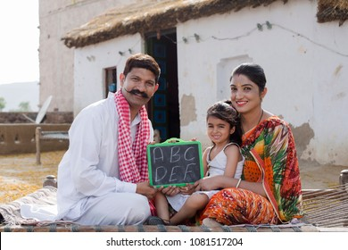 parents with daughter holding slate