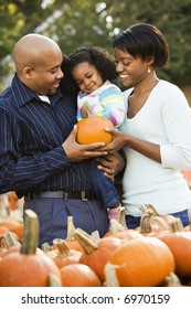 Parents and daughter picking out pumpkin and smiling at outdoor market.